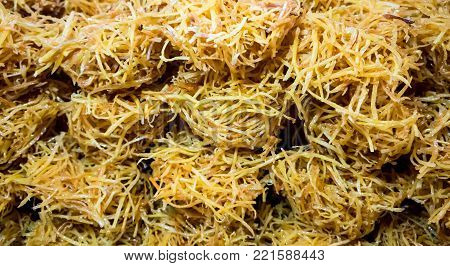 Thai crispy deep fried sweet potato straws coated with syrup, called Bird's nest. Traditional sweetmeat snack.