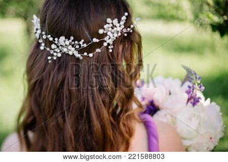 Bridesmaid with colorful wedding bouquet peonies and other flowers with professional makeup and crown tiara crest accessory turned away in purple violet dress, curled hairstyle prom graduation closeup poster