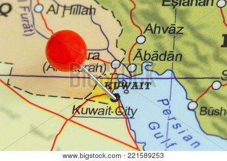Close-up of a red pushpin on a map of Kuwait City, Kuwait.