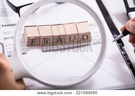 Close-up Of Person Holding Magnifying Glass And Examining Fraud Blocks On Invoice