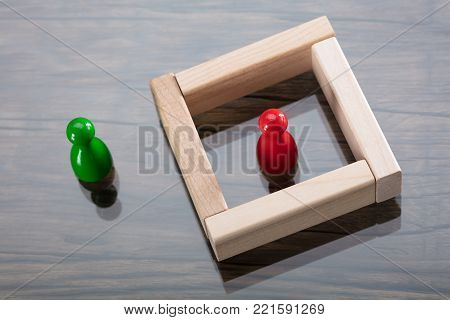 Red Figurine Pawn Surrounded By Wooden Blocks Besides Green Figurine Pawn