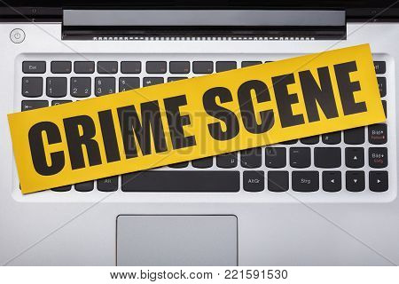 High Angle View Of Yellow Crime Scene Tape On Laptop Keypad