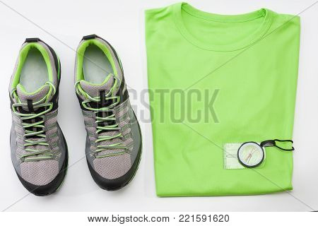 Outdoors shoes, t- shirt and magnetic compass for trail running, free running, fast climbing, hiking, studio shoot on white background