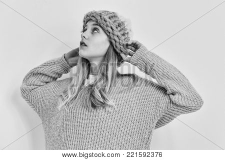 Pretty girl or cute young woman with blond hair and adorable face in fashionable blue sweater and hat isolated on white background