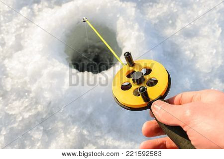 Winter fishing. Fisherman hand holding rod lowered into ice hole