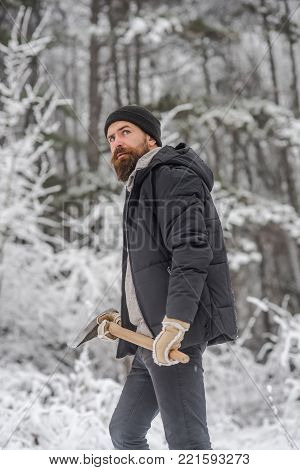 Man lumberjack with ax. Camping, traveling and winter rest. Temperature, freezing, cold snap, snowfall. skincare and beard care in winter, beard warm in winter. Bearded man with axe in snowy forest.