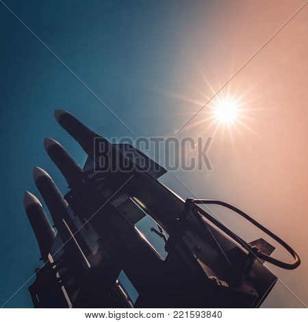 Four rockets of anti-aircraft missile system are directed upwards against the background of blue sky and sun at sunset