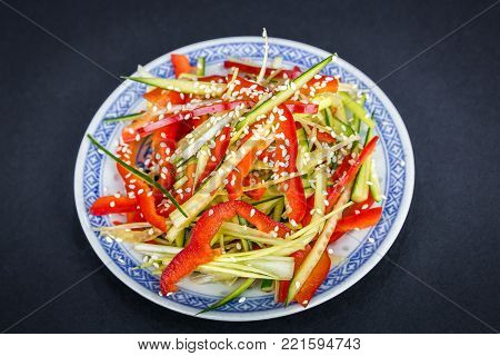 Chinese food. Vegetable spicy salad with colorful fresh paprika, leek, cucumber and sesame on black background.
