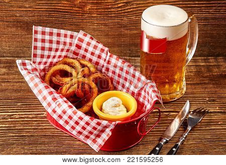 Fried breaded onion rings with sauce and glass beer on wooden table. Serving a ready meal in a restaurant, cafe, bar, pub. Still life. Copy space