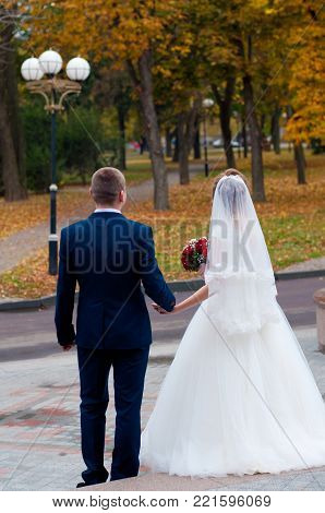 Autumn wedding. Bride with red bouquet and groom in dark suite holding hands, staying on road in park near yellow trees and nice streetlight