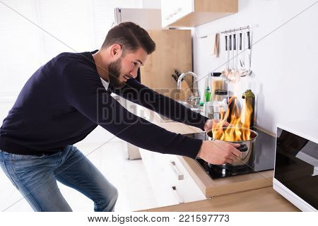Side View Of A Young Man Holding Utensil On Fire In Kitchen