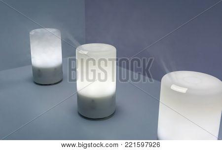 Electric aroma oil diffuser on wooden floor. Selective focus