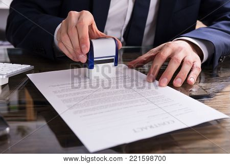 Close-up Of A Businessperson's Hand Stamping Document In Office