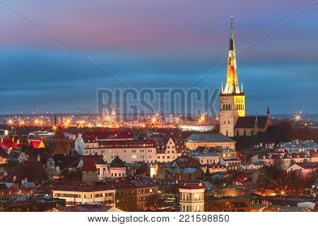 Aerial cityscape with Medieval Old Town illuminated in evening twilight and St. Olaf Baptist Church, sea and port in Tallinn, Estonia