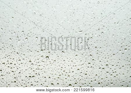 Raindrops on the glass of the window. Image in gray colors. Can be used as a background.