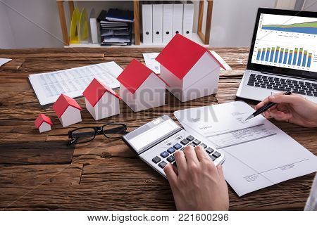 Close-up Of A Businessperson's Hand Calculating Bill With House Model And Laptop On Desk
