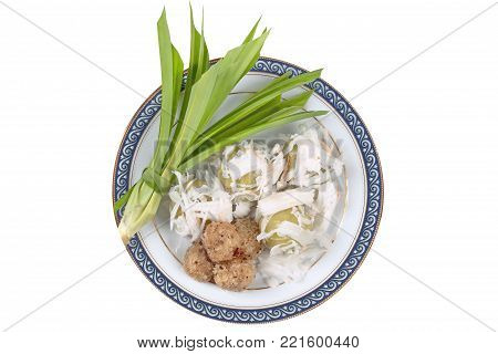Isolated of Thai dessert ,Steamed flour wrap sweet mashed coconut topped soft coconut roll with pandan leaves call Khanom Tom in Thai ,served in Thai pattern dish.