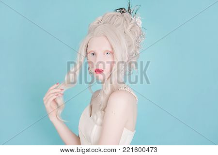Blonde woman with beautiful luxurious rococo hair style in white dress on a blue backgroun. Beautiful blonde girl with stylish make-up. Sexy blonde model. Blonde with curly hair