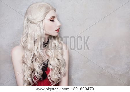 Luxurious blonde woman with beautiful long white hair and red lips on a gray background. Beautiful blonde girl with stylish make-up. Sexy blonde model. Blonde with curly hair