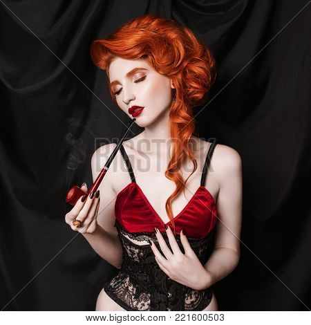 A red-haired woman in a black corset smoke a pipe on a black background. Conceptual photography with pipe for for smoke. Young woman smoke in underwear. Conceptual picture of a girl who smoke poster