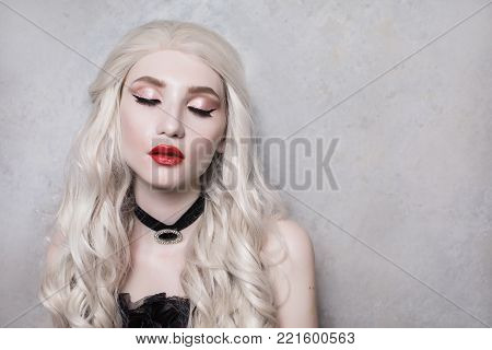 Luxurious sexy blonde woman with beautiful long white hair and red lips on a gray background. Young sexy girl. Beautiful sexy feminine model with white hair. Sexy clothes