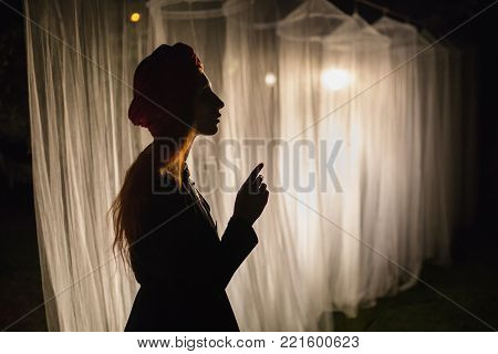 Woman silhouette. Noir silhouette. Conceptual photo with silhouette. Silhouette in the night. Silhouette on a dark background. Silhouette in front of the lantern The white long canopies are illuminated by the light of the lantern on a dark night