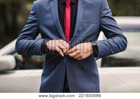 Successful businessman leader in a dark business suit with a red tie against the background of a car. Stylish leader. Fashionable watch on  hand of leader. Leader button up a button on jacket