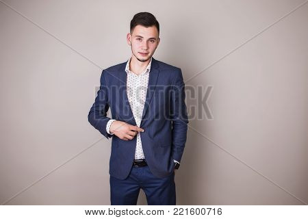 Successful businessman in business suit with a tie on gray background. Stylish businessman. Confident businessman on the background of the gray wall. Young businessman. A focused businessman on the success. Successful businessman concept