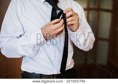 Successful businessman in business suit with a tie on background of a gray car. Stylish businessman. Confident businessman on the background of the car. Young businessman. A focused businessman on the success. Successful businessman concept