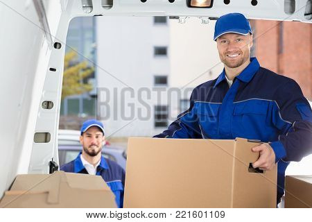 Smiling Young Male Mover Unloading Cardboard Box From Truck
