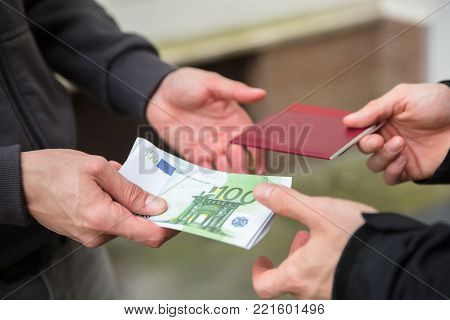 Human Hand Giving Banknote And Buying Illegal Foreign Passport