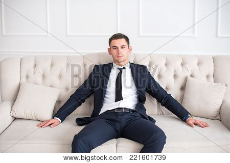 Young Serious And Confident Man In A Business Suit Sitting On The Couch