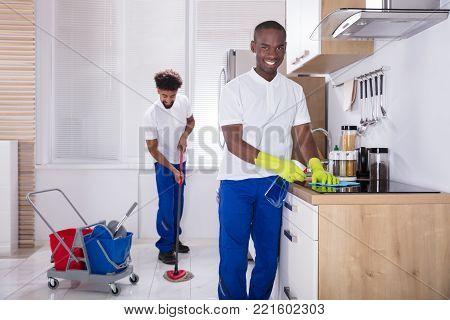 Two Smiling Male Janitor Cleaning The Induction Stove And Mopping Floor In The Kitchen