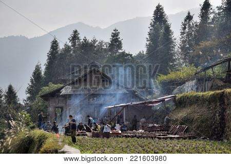 GUIZHOU PROVINCE, CHINA - CIRCA DECEMBER 2017:  A home-made pig-slaughtering on the occasion of wedding feast. An old wooden cottage and misty mountains in the background.
