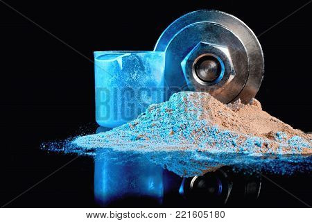 Protein powder with a measuring cup on the background of a dumbbell.  Protein mixture for athletes.