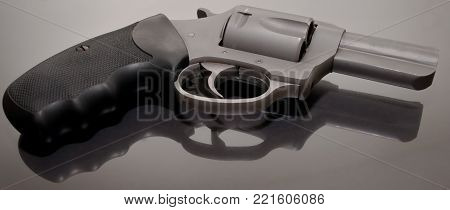 A stainless steel  revolver laying on a glass surface