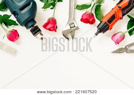 Flat Lay of Working construction tools and roses on grunge white wood. Adjustable wrench, wrenches, paint brush, screwdriver,plier,electric drill on white rustic wood background. Top view with copy space. Valentine's day and labor day with DIY constructio