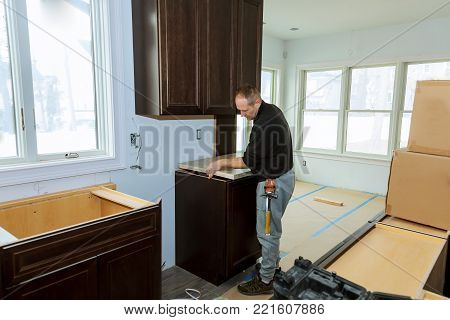 Contractor installing a laminate counter top during a kitchen remodel insrall counter top kitchen