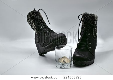 Fur winter boots on a white background. Black boot stands on a glass with coins.