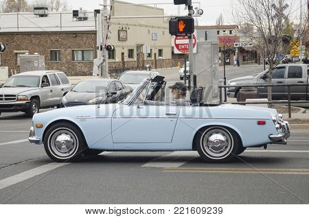 FLAGSTAFF, ARIZONA, USA- NOVEMBER 12, 2017: Old man driving a blue Datsun at the street in a cloudy day in Flagstaff, Arizona