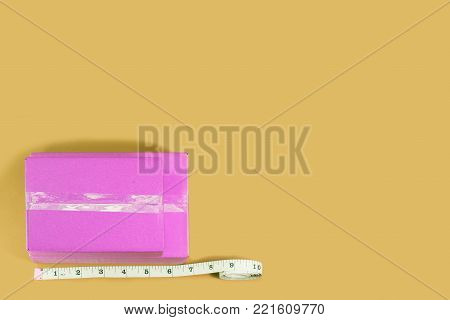Top view pink box with tape measure on yellow background.