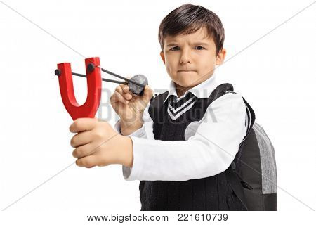 Angry little schoolboy aiming with a slingshot and a rock isolated on white background