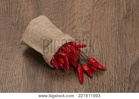 Red chili peppers on dark wooden background. Fresh chili pepper on a wooden board. Growing chili. Healthy spice.