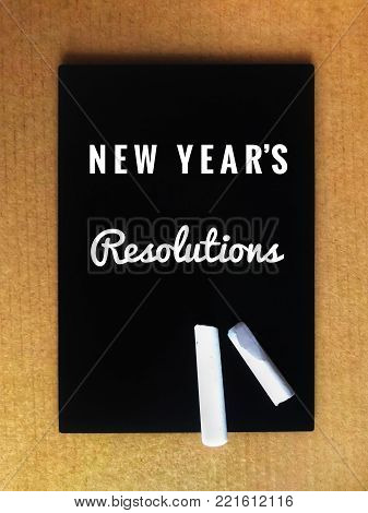 Motivational and inspirational wordings - 'New year's resolutions' written on blackboard. With vintage styled background.