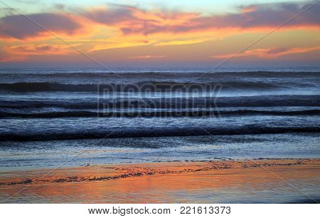 Beautiful beach sunset in Cayucos, California Central Coast with orange reflections on water and wet sand.