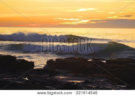Ocean waves breaking near rocks at sunset near Cambria, California.