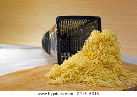 Pile of yellow cheese grated rests on a wooden stand. Still life in warm tones, the view from the side on level of eye look.