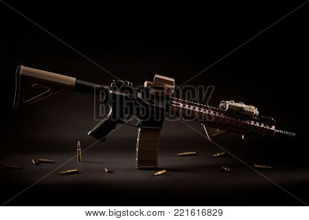 assault rifle and golden bullets on a black background