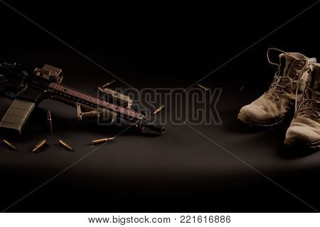 assault rifle and military boots on a black background