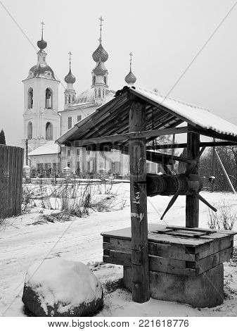 Archaic vintage wooden well on the background of the old Trinity Church in the village of Tolgobol near Yaroslavl, Russia